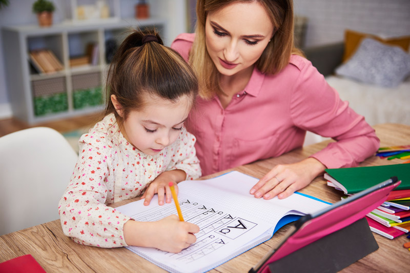 young-woman-helping-girl-with-homework-8BSC5RF.jpg